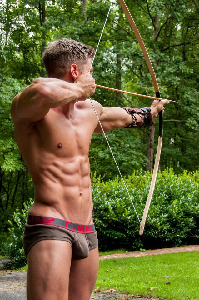 photo of man in underwear firing bow and arrow