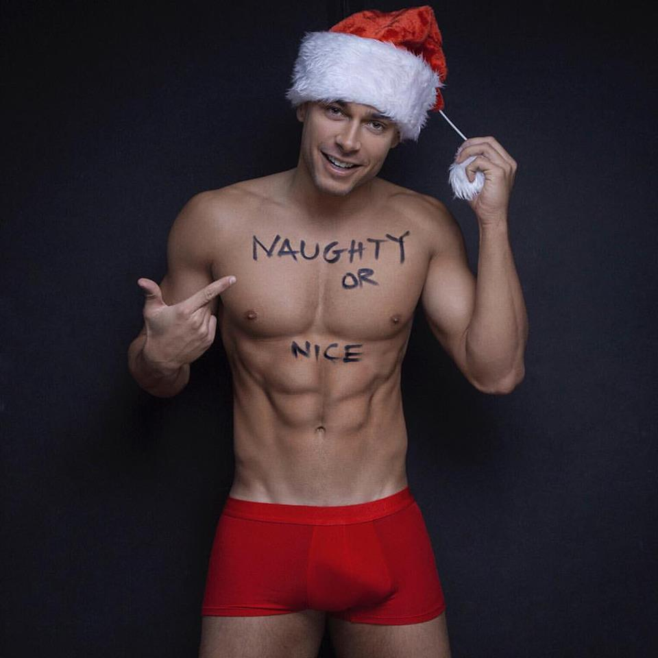 Photo of shirtless man in Santa hat