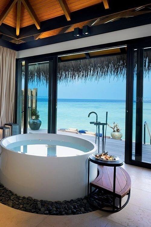 Photo of a round luxury bathtub overlooking a tropical ocean view