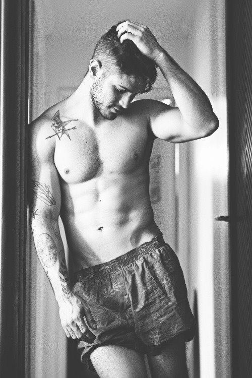 image of shirtless man with tattoos in marijuana boxer shorts