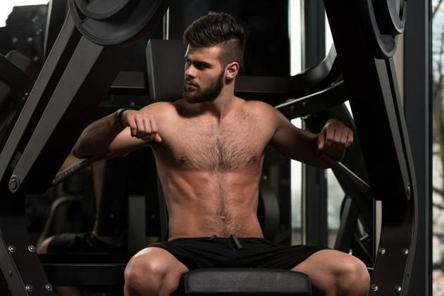 Photo of a shirtless, bearded man sitting at a chest press machine in a dark gym.