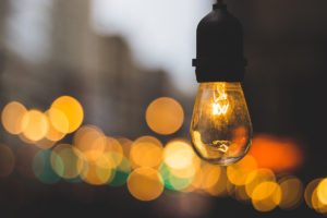 photo of a lightbulb with soft focus lights in background